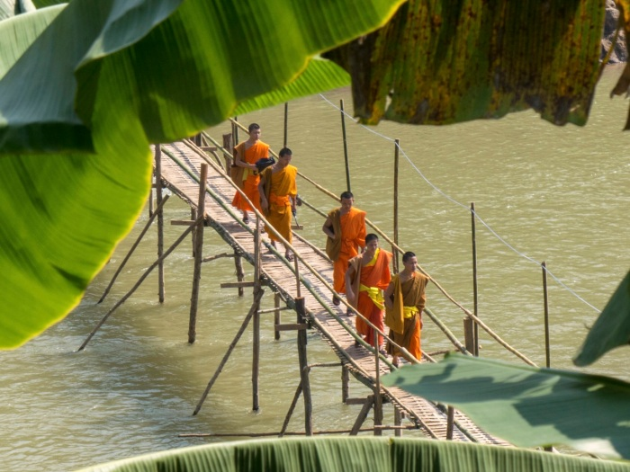 Monks crossing the bamboo bridge