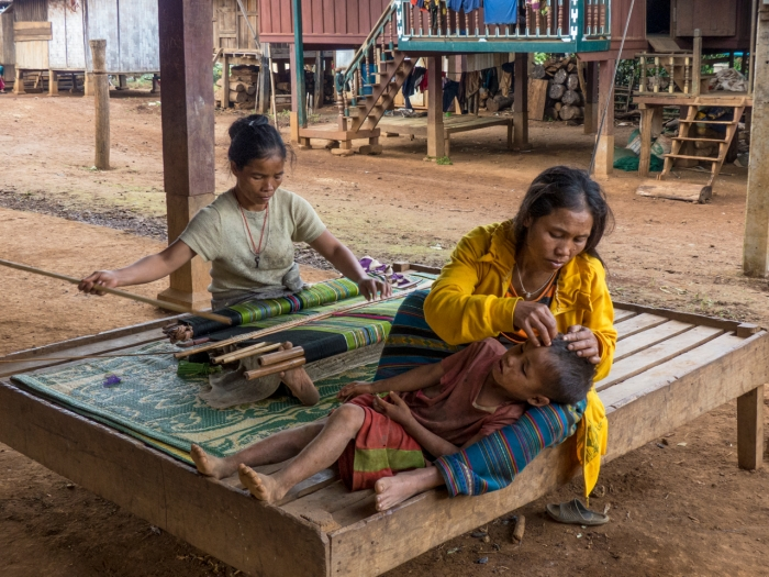 Woman weaving and another caring for child