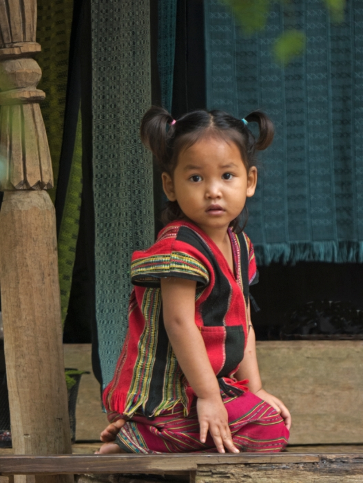 Young girl dressed in tribal weaving at Faux village