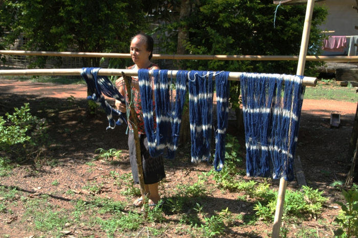 Drying her finished thread that will be used for weaving