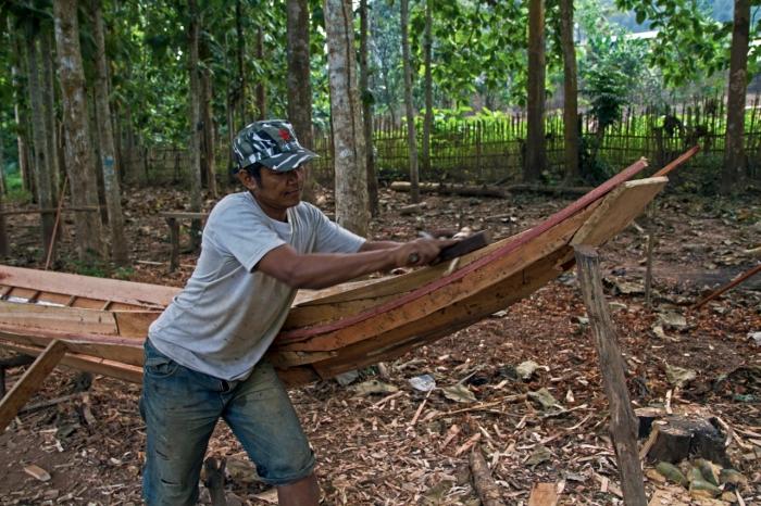 Man building a canoe near the village