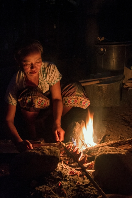 A woman cooking dinner near out hut